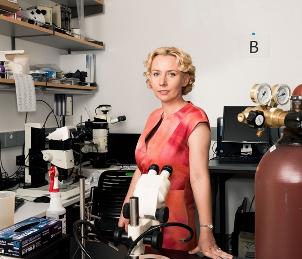 Woman standing in a lab behind a microscope
