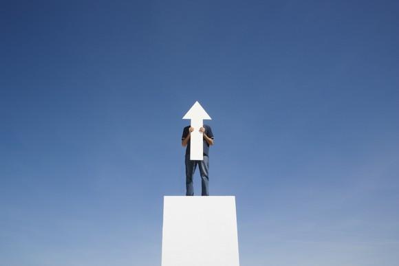 Man hiding behind an upward pointing arrow.