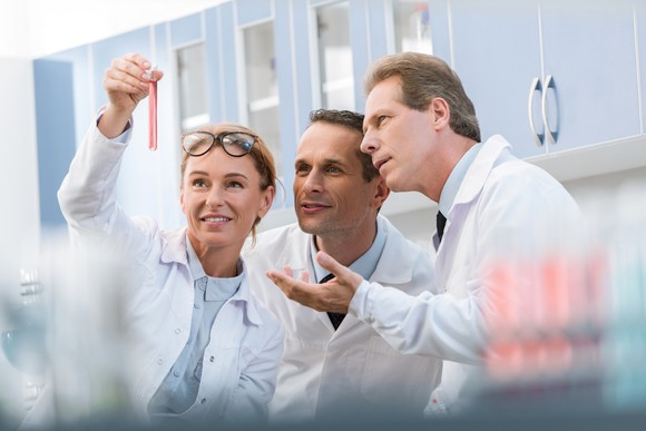Scientists discussing the contents of a test tube.