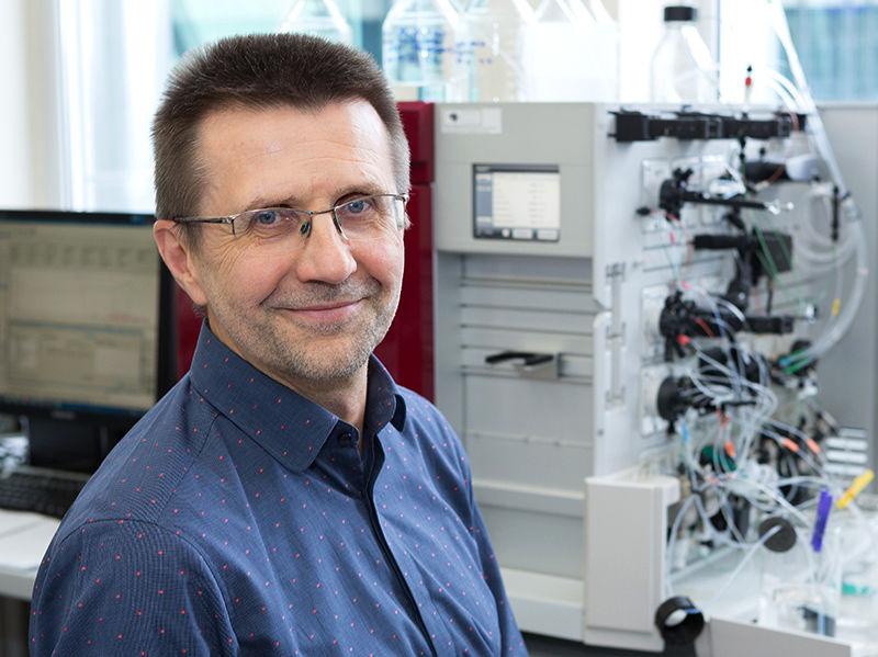 Virginijus Šikšnys smiles at the camera in a laboratory.