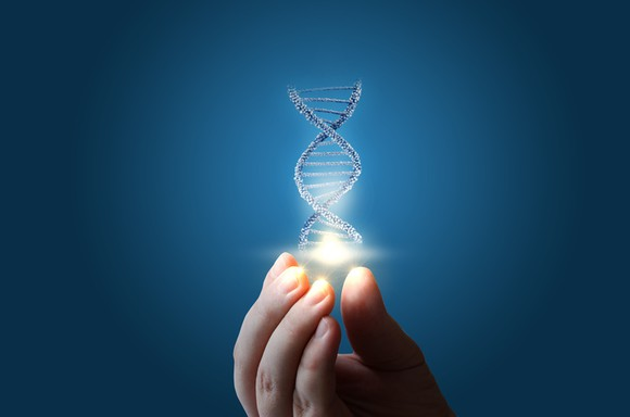 A hand with a piece of DNA floating above it